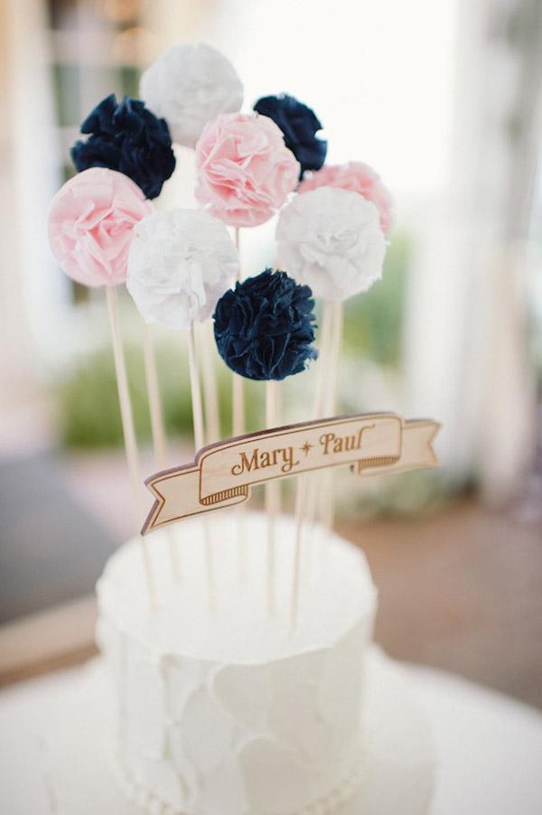 Bánh cưới ngộ nghĩnh với những chiếc tem cắm hình bông hoa bằng giấy.